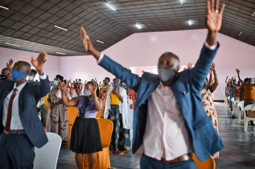congregants with arms raised in worship and prayer